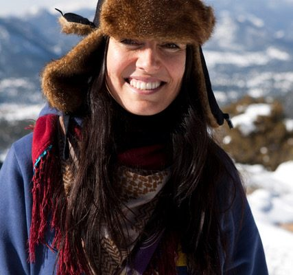 smiling woman wearing a black fur lined hat