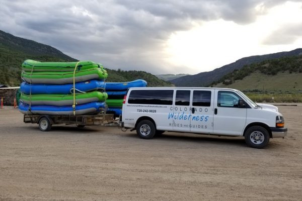branded white vans with high stacked raft trailers