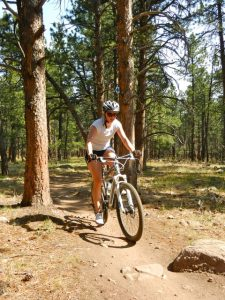woman mountain biking though a dirt forest trail