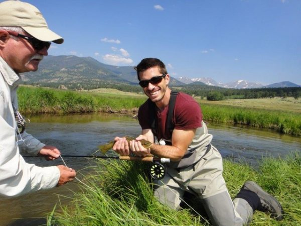 man kneeling holding a fish and his fly rod