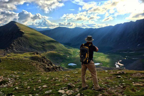 man enjoying the view hiking in mountains
