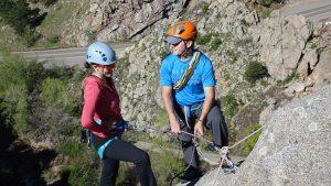 guide teaching a woman about rock climbing anchors