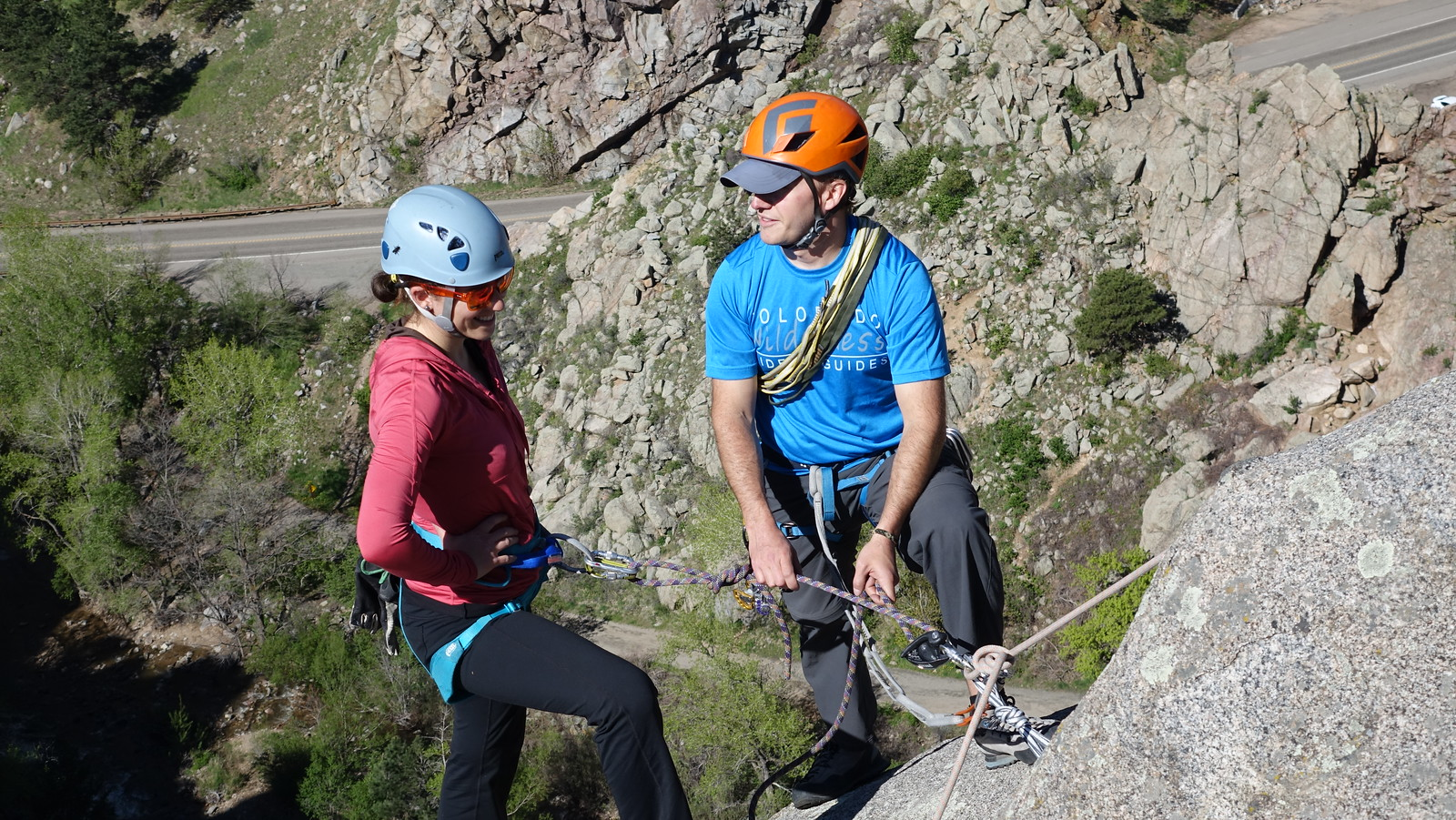 guide teaching a woman about rock climbing anchors