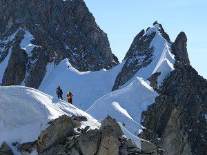 two men on a steep snowy mountain peak