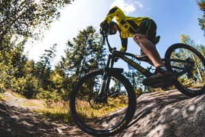 man in a yellow jersey riding over rocks on a mountain biking trail
