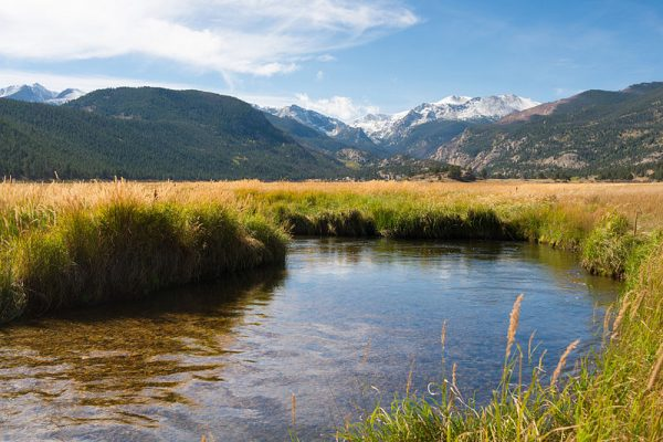 stream with snowy mountain range in the background