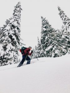 woman winter hiking up a steep snowy trail