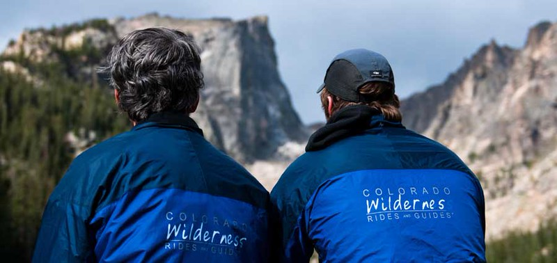 two men wearing branded blue jackets with their back to the camera