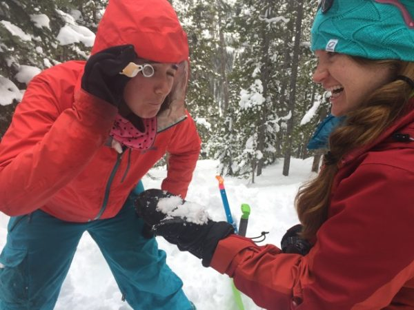 two young women being silly with a magnifier looking at snow