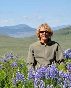 guide Brad Kahland standing in lupines with mountains in the background