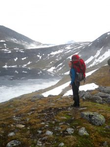 guide Hannah Rifkin wearing a large red pack on a mountain hike