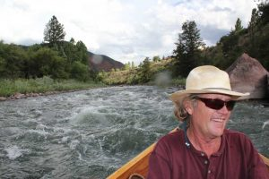 guide Jack Bruner riding some rapids in a boat