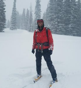 guide Joey Cararra in a red jacket on skis outside in the snow