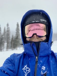 guide Tripp Arnold wearing goggles and a blue jacket in the snow