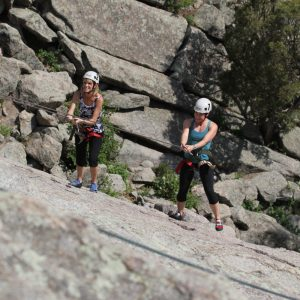 Two young women Rock Climbing Outdoors