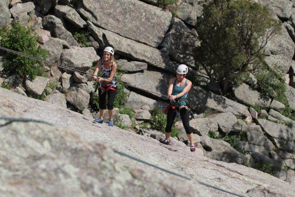 Two young women Rock Climbing Outdoors