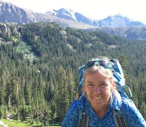 guide Cindy Gagnon wearing a pack above treeline on a mountain trail