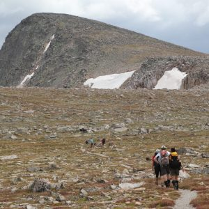group hiking up a rocky tallus field