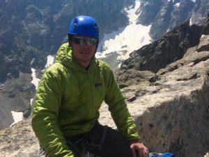 guide Dave Hansen wearing a climbing helmet sitting on rocks