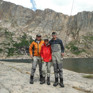 father and two sons posing in their fly gear with rods next to a mountain lake