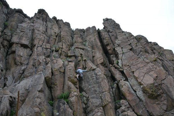 man top rope rock climbing up a steep rock formation