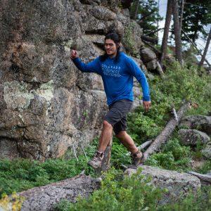 man walking along a fallen tree wearing branded blue hoodie