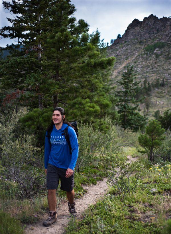 man wearing branded blue hooded walking on a trail