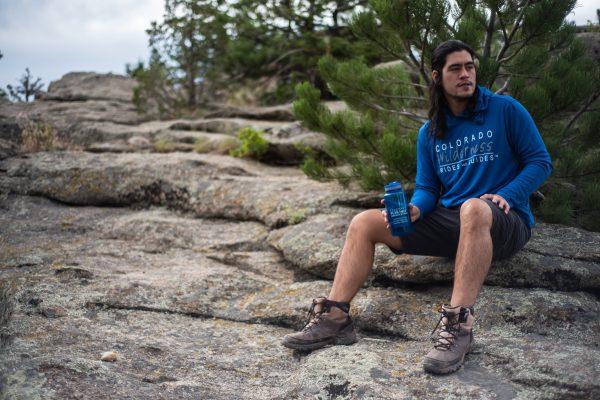 man sitting on a rock wearing a branded blue long sleeve holding branded blue water bottle