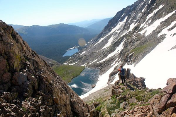man in high alpine country enjoy the view of lakes below