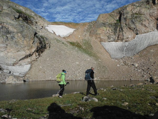 man and woman hike in high alpine country