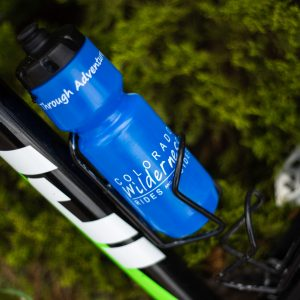 branded blue plastic squeeze water bottle on a mountain bike