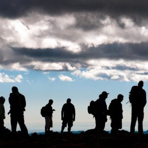 silhouette of a group on top of a mountain at dusk