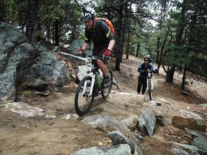 man working on rocky mountain biking skills while a woman holds her bike and watches