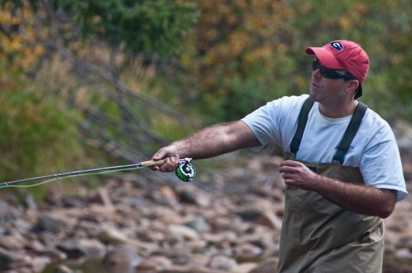 man practicing casting with his fly rod