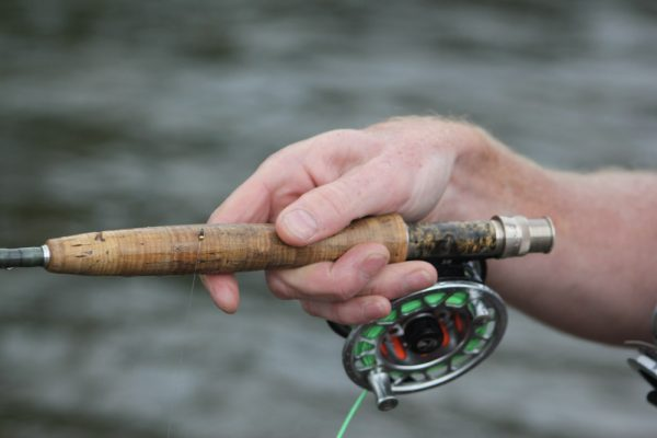 close up of a mans hand holding a fly rod