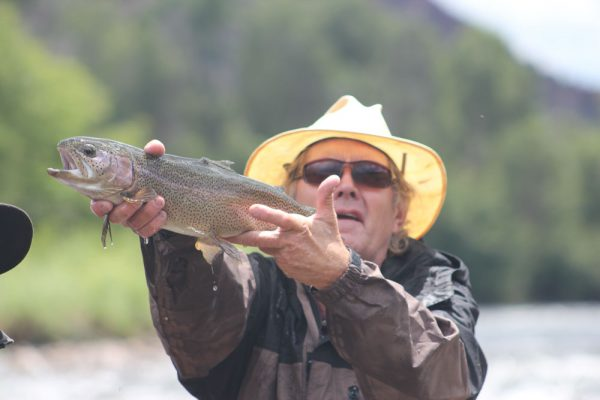 man wearing a sun hat holding the trout he caught fly fishing