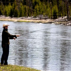 man standing on the shore casting his fly rod into water