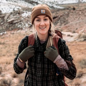 guide Jessica Bailey outside wearing a hat, pack and mittens