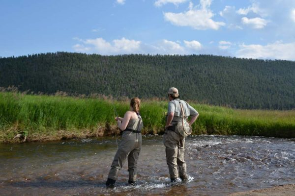 two people standing in shallow water fly fishing