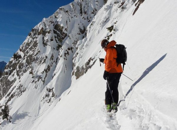 man backcountry skiing on a steep snowy mountain
