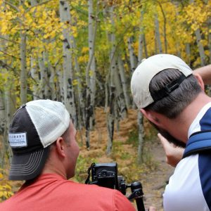 two men practicing camera settings in an aspen tree grove