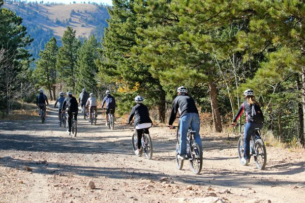group of bikers riding on a dirt road