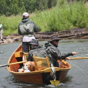 fly fishing group and dog casting from a wooden boat