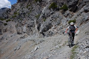 man riding up steep rocky terrain on his mountain bike