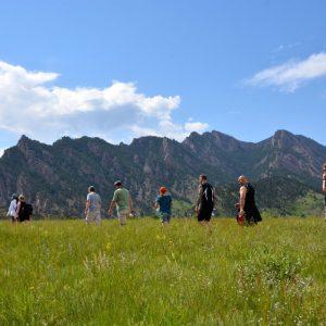group walking in a meadow below mountain foothills