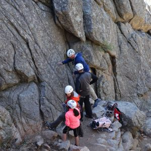 group learning how to belay and rock climb at the bottom of a climb