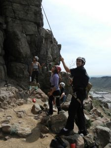 young man belaying a rock climber while other look up at the climber