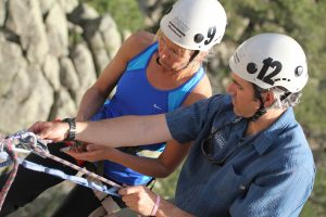 guide teaching a climber about knots while hanging off a rock anchor