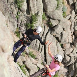 two girls high five-ing as they repel down from rock climbing