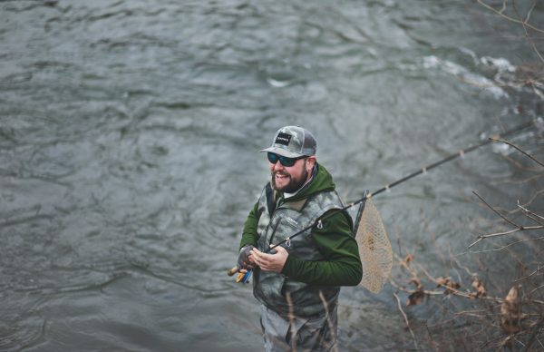 smiling man holding his net and fly rod standing at the waters edge